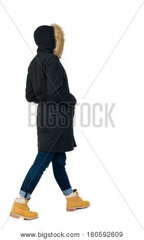 Back view of going  woman in parka. walking young girl. Rear view people collection.  backside view of person.  Isolated over white background. The girl in a jacket goes with his hands in his pockets