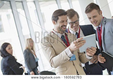 Businessmen using digital tablet at convention center