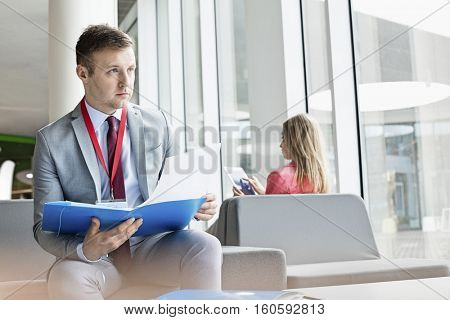 Thoughtful businessman holding file while sitting at lobby in convention center