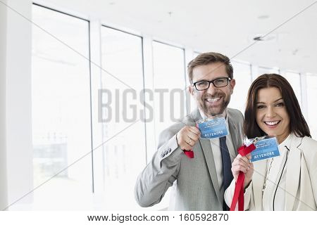 Portrait of happy business people showing identity cards in convention center