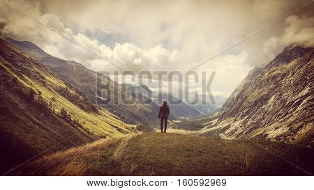 Hiker stood on the edge of a Hill looking down the Aosta Valley