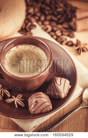 Cup fragrant hot coffee with bean chocolate sweet and loaf in vintage rustic style on wooden board for bracing morning breakfast