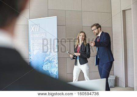 Confident business people discussing while walking in convention center