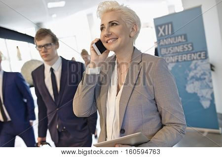 Happy businesswoman using smart phone at convention center
