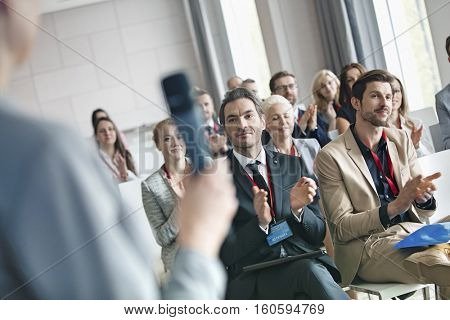 Business people applauding for public speaker during seminar