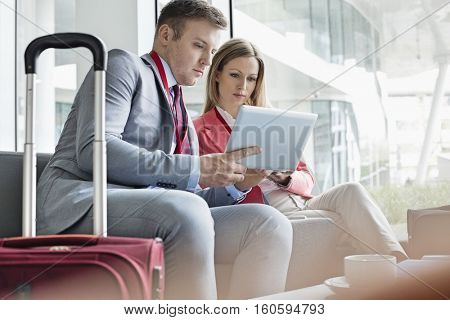 Business people using digital tablet while sitting at lobby in convention center