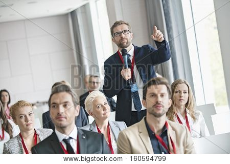 Businessman gesturing while asking question during seminar in convention center