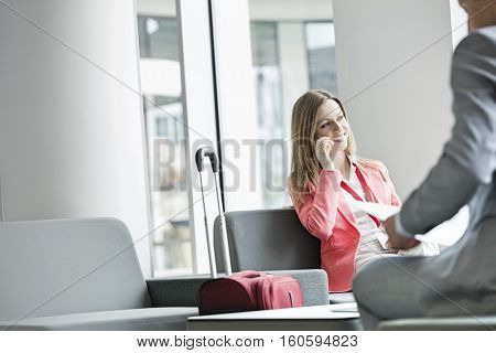 Smiling businesswoman using smart phone while sitting at lobby in convention center