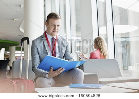 Portrait of confident businessman holding file while sitting at lobby in convention center