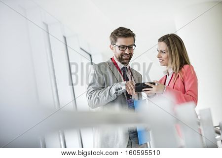 Smiling business people using smart phone in convention center
