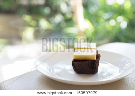 cream cheese brownie on white plate with green bokeh background selective focus
