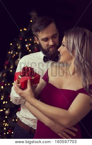 Beautiful young couple in love hugging and exchanging Christmas gifts. Focus on the guy