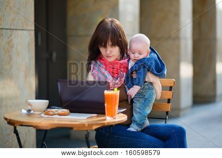 Young Mother With Her Baby Boy Working In Cafe