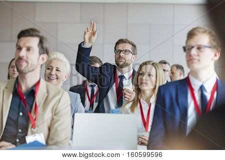 Businessman raising hand during seminar at convention center
