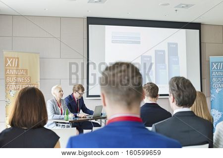 Business people sitting in seminar hall at convention center