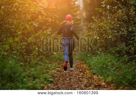 Blonde woman running among trees
