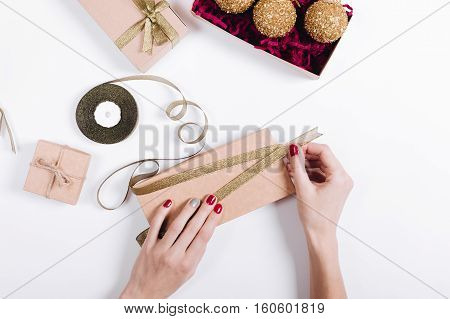 Female Hands With Red Manicure Pack The Gifts In Boxes And Tie Them With Ribbons