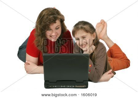 Mother With Daughter Looking To Computer