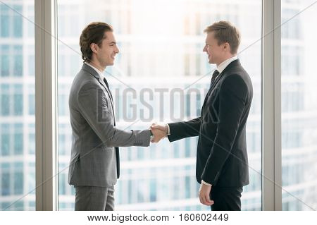 Side view portrait of two smiling business partners making agreement, taking a big deal and shaking hands in meeting room at office. Urban style glass office building in big city on the background