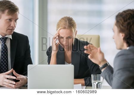 Young stressed businesswoman suffering from headache at important business meeting. Looking with doubtful expression at laptop screen, disagree with proposal or contract conditions, colleagues arguing