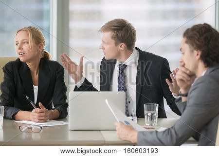 Furious boss scolding young frustrated interns with bad work results. Ineffective office workers sitting at the table and listening to irritated boss yelling with bored and annoyed expressions