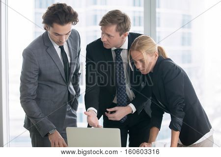 Group of three business partners discussing new project at meeting in office room, using laptop. Middle aged businessman explaining idea showing presentation on laptop screen. Business success concept