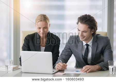 Group of two business partners discussing new project at meeting in office room, using laptop. Middle aged businesswoman and her young colleague browsing presentation on screen. Business concept