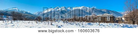 Ski slopes, houses and snow mountains landscape panorama in bulgarian ski resort Bansko, Bulgaria