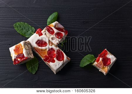 Soft Nougat With Tropical Fruit And Berries On Black Wooden Table