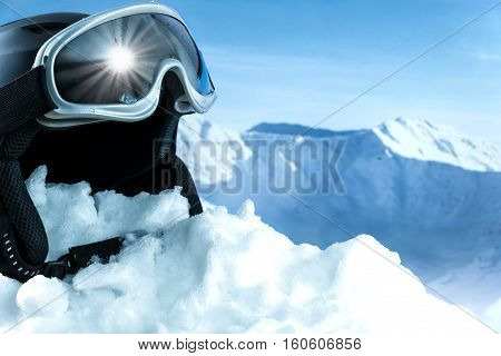 Helmet and ski goggles on snow with a blue sky and mountains