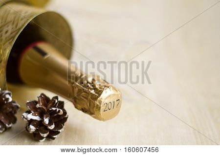 The bottle of champagne with gold glossy ribbon and natural cone. 2017 Happy New Year concept.Copy space