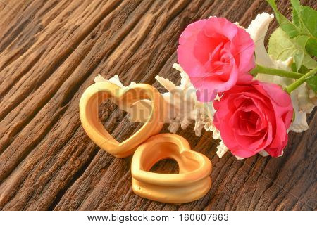 The wood hearts ,big sea shell behind the pink rose on bark.