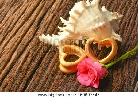 The wood hearts ,big sea shell and pink rose on bark.