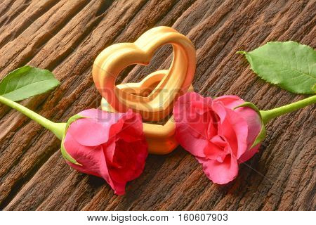 The wood hearts and two pink rose on bark.