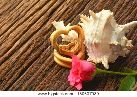 The wood hearts ,sea shell and two pink rose on bark.