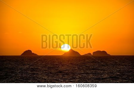 Beautiful golden sunset with the big round sun going down behind the mountain with orange vast sky, dark water of Atlantic Ocean and silhouettes of mountains at Ipanema beach, Rio de Janeiro, Brazil