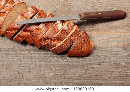 Fresh bread with knife on wooden background