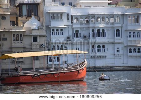 Buildings and an orange boat along lake Pichola in Udaipur, Rajasthan, India
