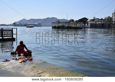 UDAIPUR, RAJASTHAN, INDIA, FEBRUARY 07, 2016 - Unidentified indian woman washing her clothes in the waters of lake Pichola