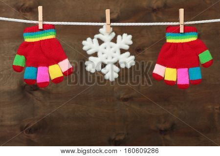 Gloves with snowflake hanging on the clothesline on brown wooden background