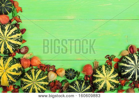 Small striped pumpkins on green wooden background