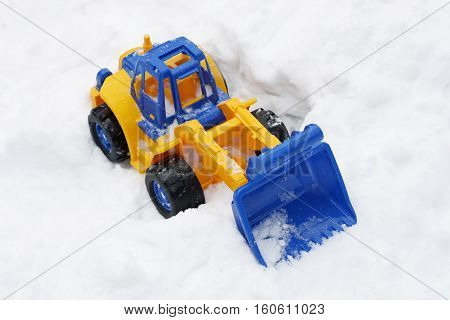 Great children's bright toy excavator which stands on the ground in the snow.