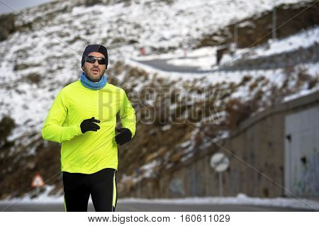 young healthy sport man running on road at snow mountains in trail runner hard workout in energy and endurance concept with a beautiful cold winter background
