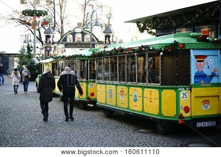COLOGNE, GERMANY - NOVEMBER 24: A locomotive-like vehicle with trailers for city tours parked on the Christmas market at the Heumarkt in Cologne's old town on November 24 2016 in Cologne.