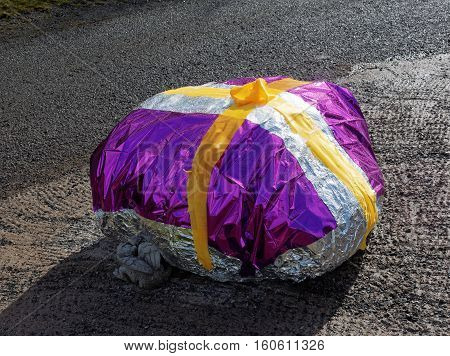 A large boulder has ben covered in foil and coloured cellophane finishd off with a yellow ribbon for an Easter Egg competition at Garth Holiday Park Machynlleth Powys Wales.