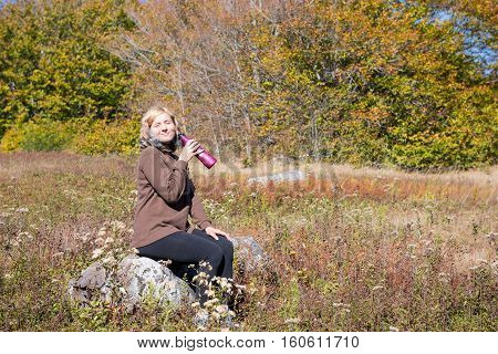 Young woman sitting on rock in meadow drinking water from bottle and smiling