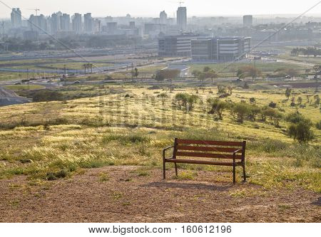 Bench on a hilltop overlooking the Be'er Sheva city in the Negev desert Israel