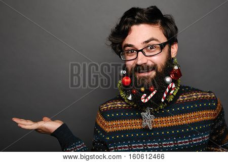 Handsome man wearing eyewear showing something on the palm of her hand. Christmas decorated beard with toys. IT geek presenting copy space