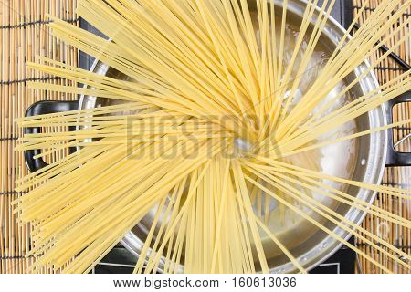 Spaghetti boiling in pan on electric stove / cooking spicy spaghetti concept