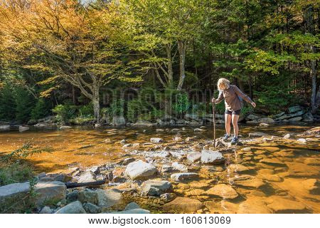 Young woman with stick crossing Red Creek river in Dolly Sods, West Virginia